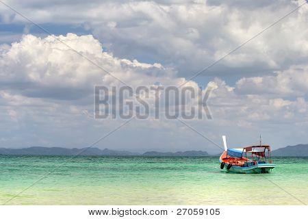 a boat on the colorful andaman sea with  cloudy sky, ko-bulon island, thailand