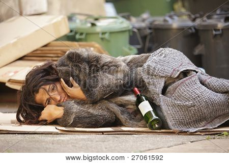 poor woman tramp lying among bin with wine bottle