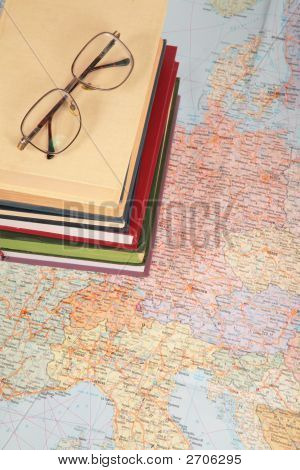 Glasses On Pile Of Books On Map Of Europe