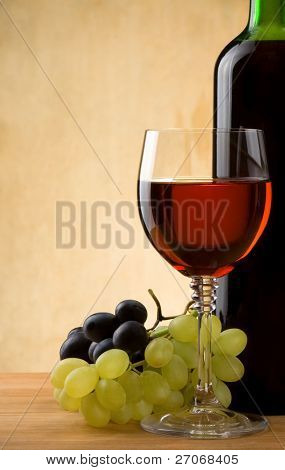 glass of red wine and bottle with grape on wood background