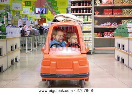 Children In Toy Automobile In Supermarket
