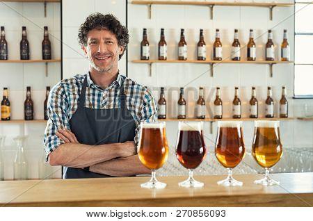 Smiling bartender wearing apron standing
