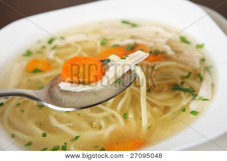 A picture of a bowl of traditional Polish chicken soup served in a bowl over wooden background