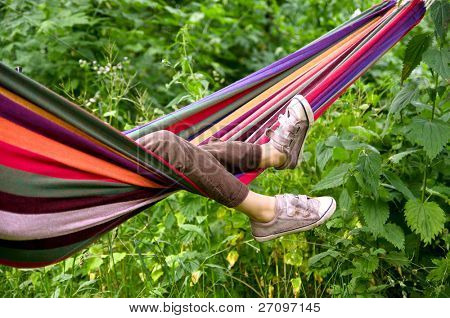small child lying in a hammock in the woods