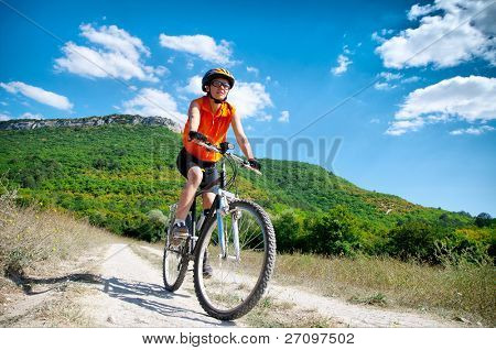 young athletic girl rides a bicycle on a mountain road