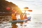 Happy Family Is Walking At Sunset Sea By Kayak Or Canoe. Active Tourism Concept poster
