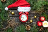 Red Alarm Clock With Arrow On 12 Hours, Santa Claus Cap, Fir Tree Branches And Different Toys On Age poster