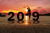 Greeting Card 2019 Happy New Years. Silhouette Of Healthy Young Woman Practicing Yoga On Tropical Be poster