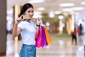 Joyful Young Woman Holding Shopping Bags And Blank Credit Card On Shopping Malls Background With Cop poster