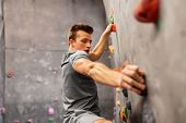 fitness, extreme sport, bouldering, people and healthy lifestyle concept - young man exercising at i poster