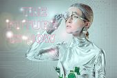 Futuristic Silver Cyborg Adjusting Eye Prosthesis And Looking At The Future Is Now Lettering Isolate poster