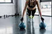 Determined Sportswoman In Weightlifting Gloves Doing Plank Exercise On Kettlebells At Sports Center poster