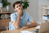 Exhausted Male Worker Yawn At Workplace Feeling Unmotivated poster
