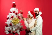 Christmas, Winter, New Year Concept. Family Decorating Christmas Tree. Happy Husband And Wife Celebr poster