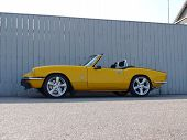 pic of spitfire  - Bright yellow Triumph Spitfire sportscar against grey fence - JPG