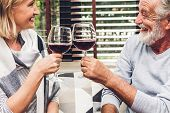 Senior Couple Relax Talking And Drinking Wine Glasses Together On Sofa In Living Room At Home.retire poster