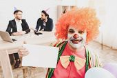 Young Man In Clown Costume On Meeting In Office. April Fools Day. Businessman In Office. April Jokes poster