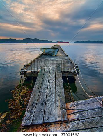 Rickety Island Dock With Mountains And Tankers In Distance