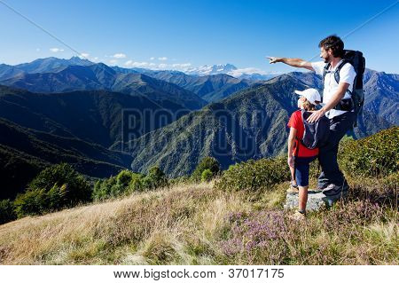 Man and young boy standing in a mountain meadow. The man points to a direction, showing something to the boy. Summer season, clear blue sky. Monte Rosa Massif, Piemonte, west italian Alps.