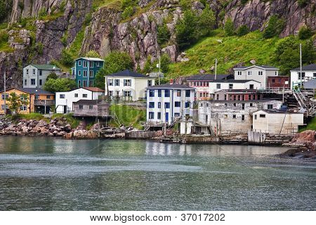 Colorful houses on the rocky shore of Signal Hill facing the harbour in St. John's, Newfoundland, Canada. A section of town known as the Lower Battery.