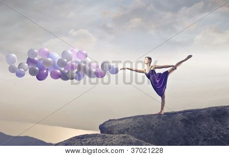 Blonde dancer stepping on a rock holding some balloons