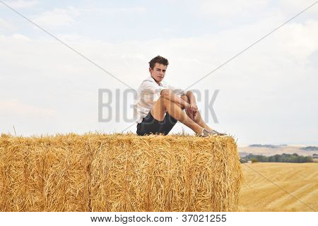 Boy on some sheaves looking at someone