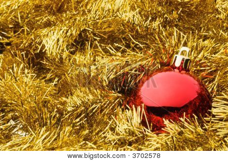 Red Christmas Ball Over Gold Tinsel Garland
