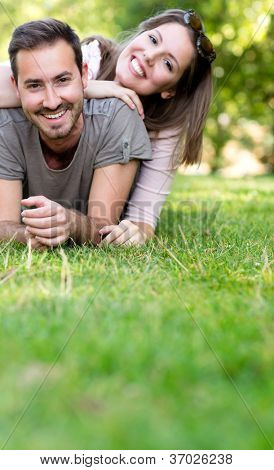 Playful couple smiling and lying at the park