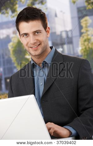 Smiling businessman sitting outside of office building, using laptop computer, looking at camera.