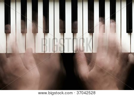 Hands playing piano. Motion blur