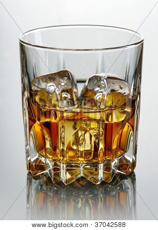Glass of whiskey and ice  over dark background