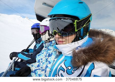 Three skiers in special clothing and helmets ride on cable car in mountains.
