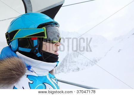 Rapt female skier in special clothing rides on funicular in mountains.