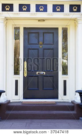 Colonial style black door on white house with  gold ornamentation above