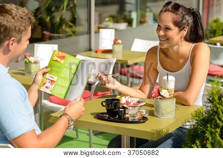 Couple eating looking at menu cafe restaurant smiling woman