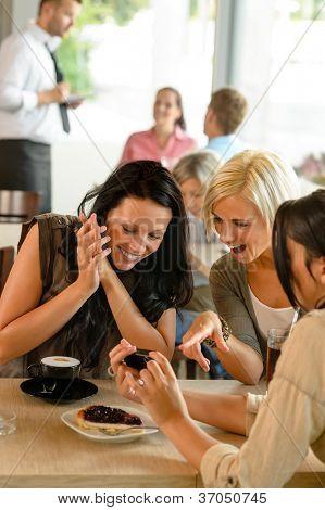 Amigos mirando fotografías y riendo divertido de mujer café disfrutando