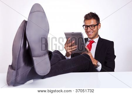 young business man sitting at his desk and reading on his electronic tablet pad