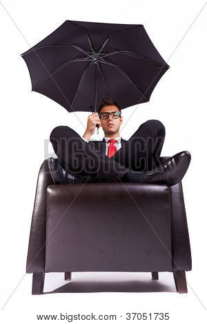 Image of a business man sitting in comfortable armchair with an umbrella in his hand