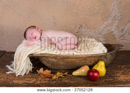 Sleeping newborn baby of 11 days old in a grunge wooden dough bowl