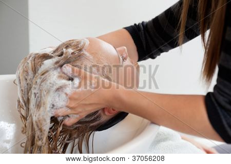 Beautician washing off shampoo from woman's hair at beauty spa