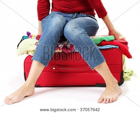 The girl is trying to close suitcase crammed on white background