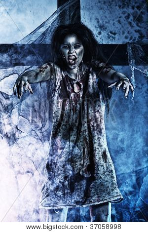 Bloodthirsty zombie standing at the night cemetery in the mist and moonlight.
