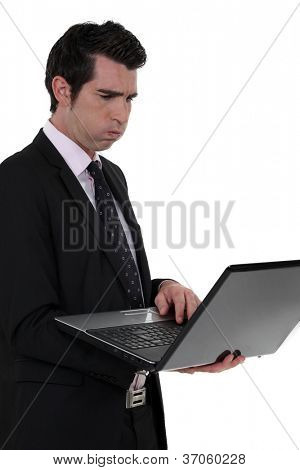 An unhappy businessman with a laptop.