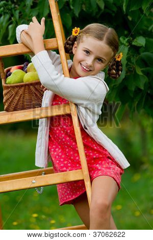 Autumn orchard - lovely girl with ripe fruits in basket