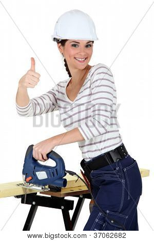 Upbeat woman using band-saw