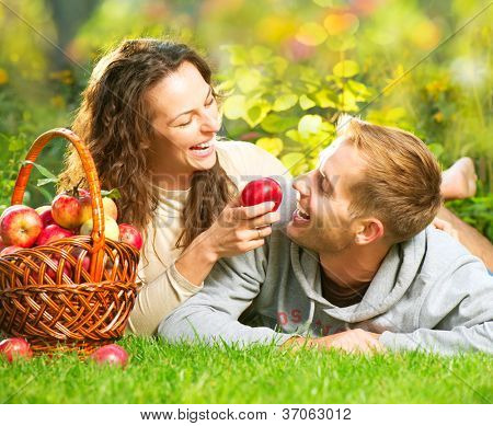 Happy Smiling Couple Having Fun on the Grass and Eating Apples in Autumn Garden.Healthy Food.Outdoor.Park.Basket of Apples.Harvest concept. Diet