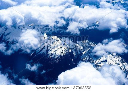 Mountain view from the top through the clouds.   The mountain peaks covered with snow. View from airplane. blue tint