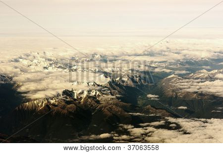 Mountain view from the top through the clouds.   The mountain peaks covered with snow. View from airplane. sunlight tint
