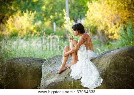 nude woman sit with a cigareton stones against nature background