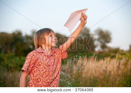 Boy with paper plane in the field